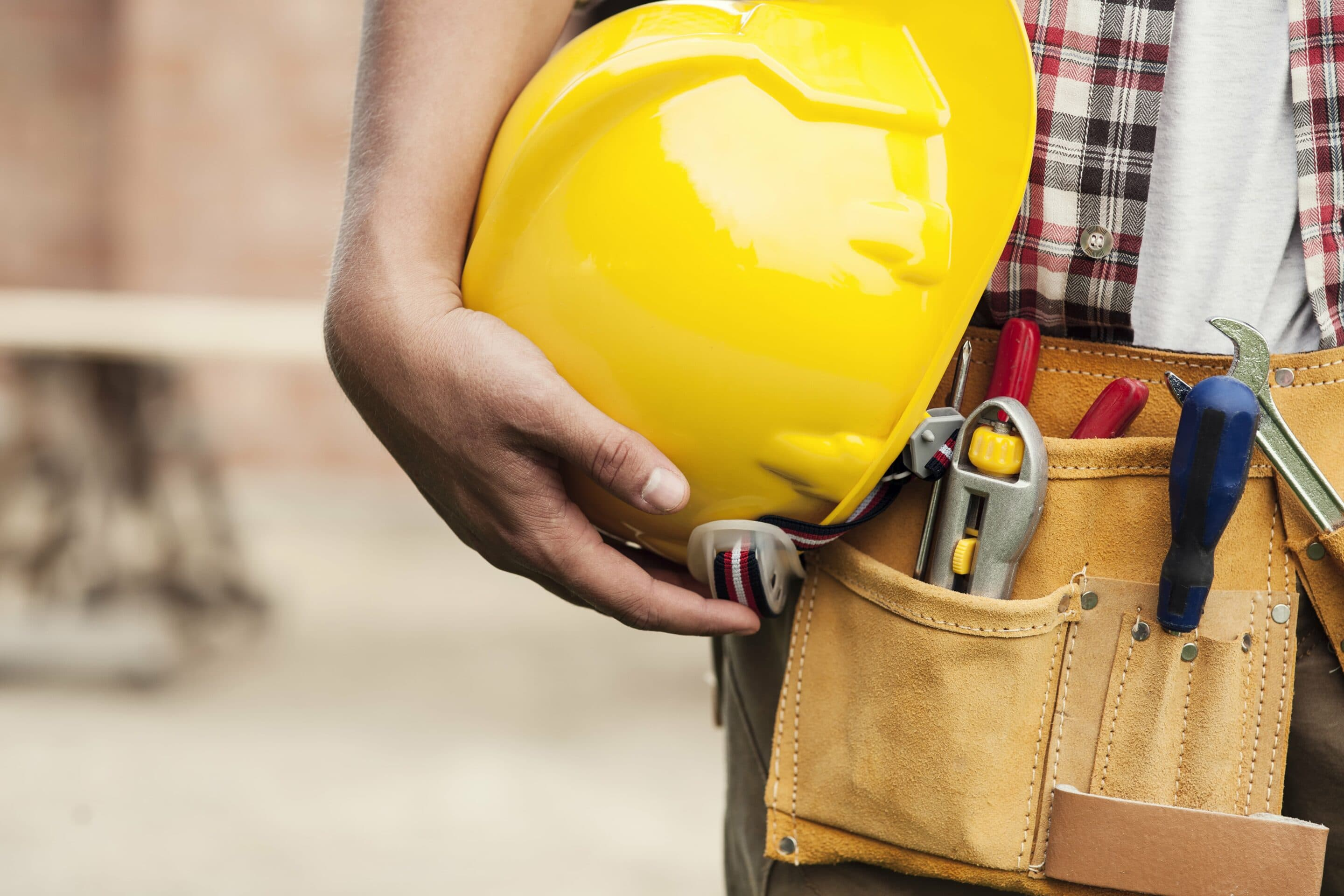 Close up of a workers tool belt and hard hat.