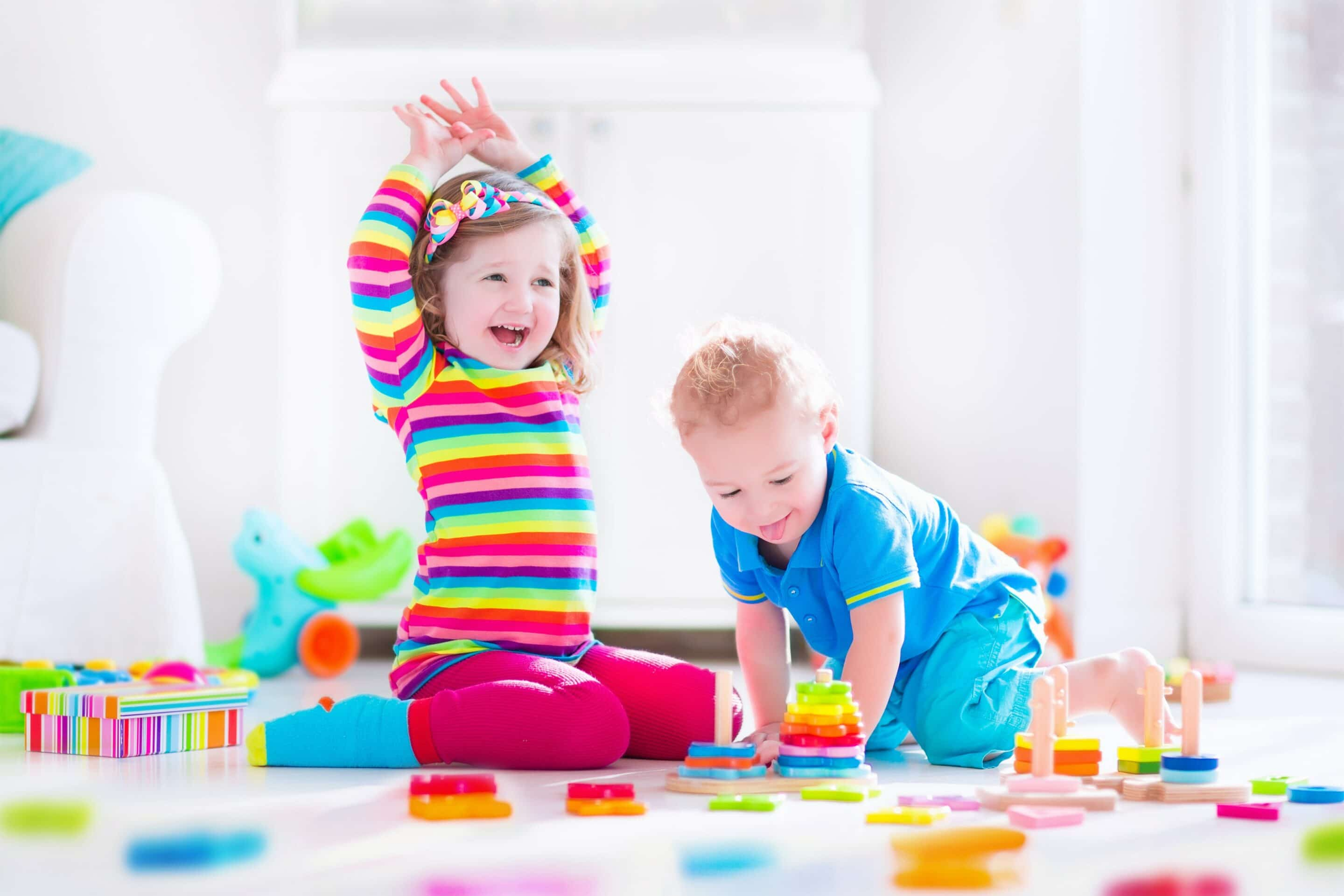 Two young children playing on a mat with coloured blocks.