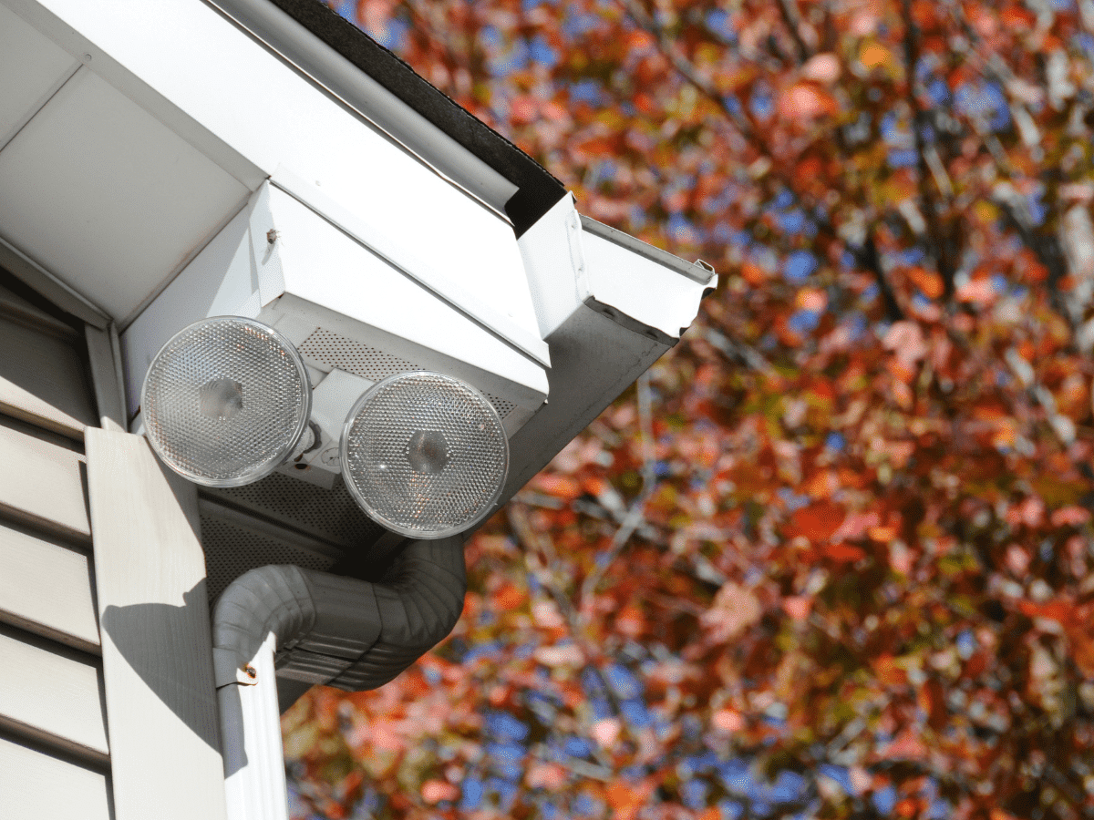 Sensor security lights attached to the corner of the outside of a house.