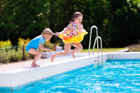 two children jumping into a swimming pool